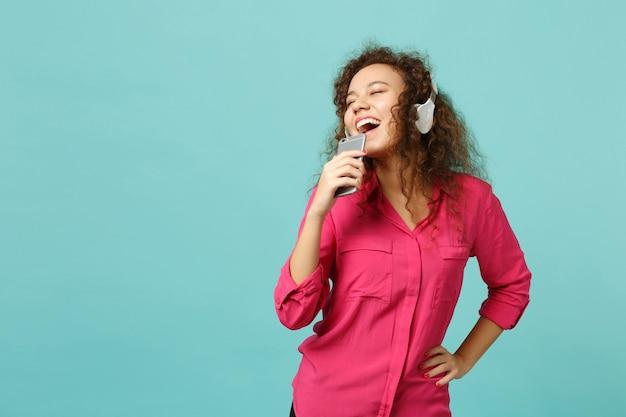 Vrolijk afrikaans meisje in casual kleding houdt mobiele telefoon vast, luister muziek met koptelefoon geïsoleerd op blauwe turkooizen achtergrond in studio. mensen oprechte emoties levensstijl concept. bespotten kopie ruimte.