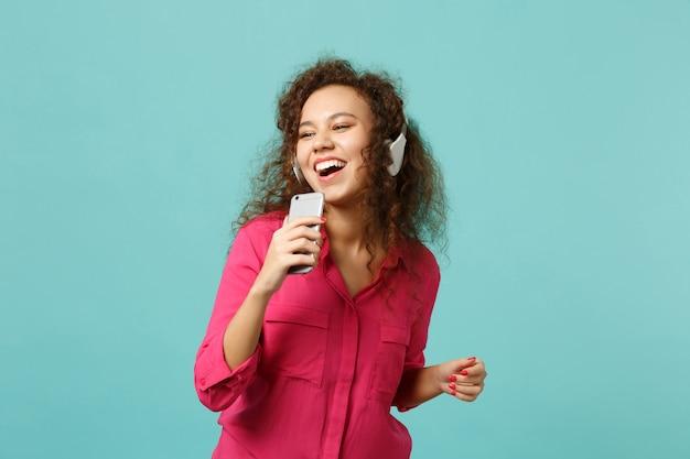 Vrolijk afrikaans meisje in casual kleding houdt mobiele telefoon vast, luistert muziek met koptelefoon geïsoleerd op blauwe turkooizen achtergrond in studio. mensen oprechte emoties levensstijl concept. bespotten kopie ruimte.