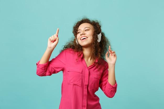 Vrolijk afrikaans meisje in roze casual kleding luisteren muziek met koptelefoon en dansen geïsoleerd op blauwe turquoise muur achtergrond. mensen oprechte emoties, lifestyle concept. bespotten kopie ruimte.