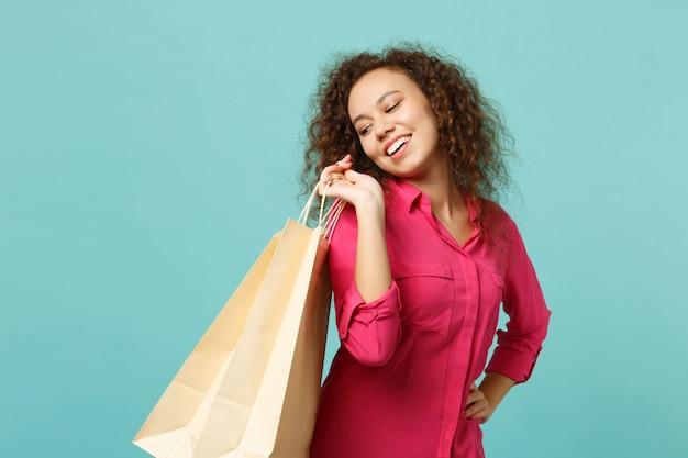 Vrolijk afrikaans meisje in roze vrijetijdskleding met pakketzak met aankopen na het winkelen geïsoleerd op blauwe turquoise muurachtergrond. mensen oprechte emoties levensstijl concept. bespotten kopie ruimte.