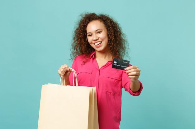 Vrolijk afrikaans meisje in vrijetijdskleding houdt pakkettas met aankopen vast na het winkelen met creditcard geïsoleerd op blauwe turkooizen achtergrond. mensen oprechte emoties levensstijl concept. bespotten kopie ruimte.