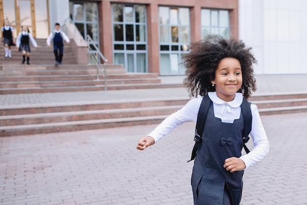 Vrolijk afrikaans schoolmeisje rent vreugdevol de trap op van school.