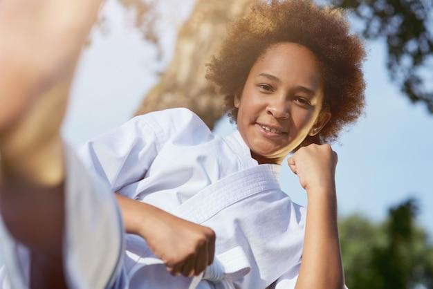 Vrolijk afro-amerikaans meisje dat buitenshuis vechtsporten beoefent