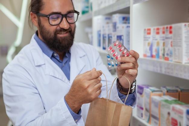 Vrolijk apotheker verkopend medicijn bij zijn drogisterij