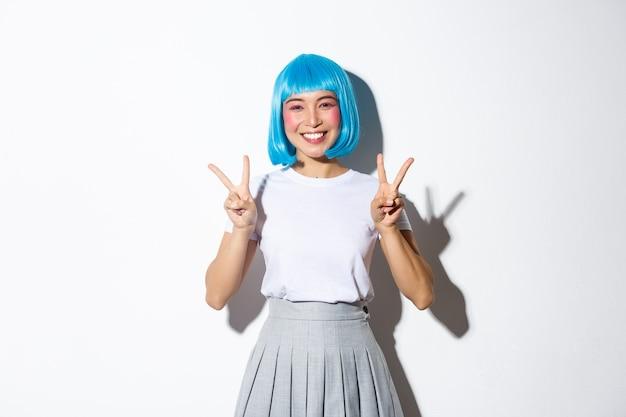 Vrolijk aziatisch meisje in blauwe feestpruik, ziet er schattig uit in halloween-kostuum en toont vredesgebaren, staande kawaii.
