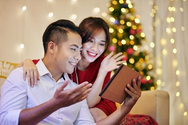 Vrolijk aziatisch stel wenst hun familie prettige kerstdagen bij het maken van videogesprekken via tabletcomputer