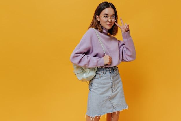 Vrolijk aziatisch tienermeisje in een stijlvolle spijkerrok en paarse trui laat een v-zucht zien en houdt een mintrugzak op een oranje geïsoleerde muur