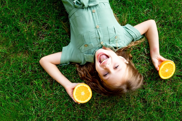 Vrolijk babymeisje in de zomer op het gazon met sinaasappels op het groene gras, plezier en vreugde, ruimte voor tekst