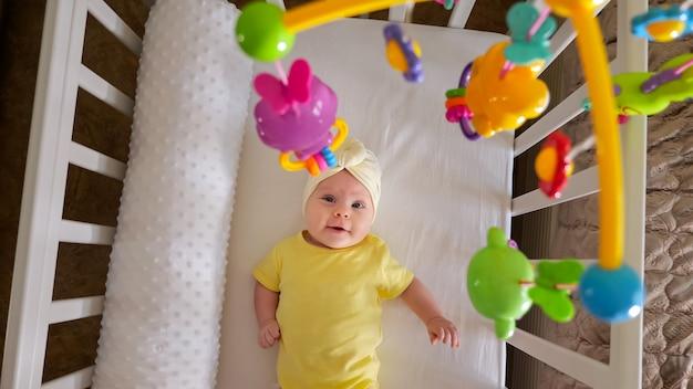 Vrolijk babymeisje in gele kleding en witte muts ligt in het kinderbed en kijkt nieuwsgierig naar de hangende mobiel in het bovenaanzicht van de appartementkamer