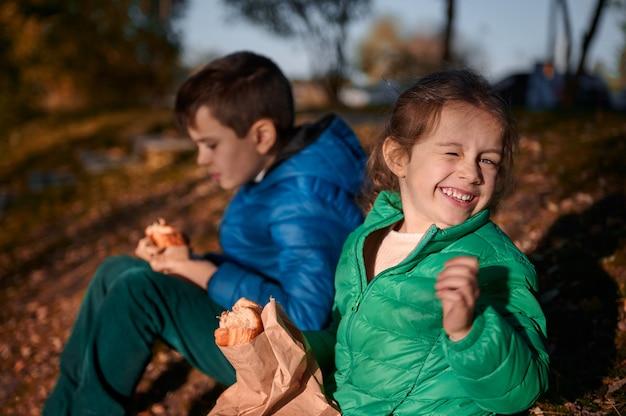 Vrolijk babymeisje met een groene jas zit dicht bij haar broer aan de rivieroever, houdt een gebakken croissant vast en lacht schattig naar de camera, genietend van een mooie zonnige warme herfstdag in de natuur