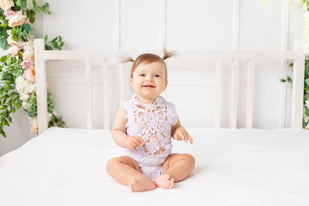 Vrolijk babymeisje zes maanden oud zittend in een heldere mooie kamer op een wit bed