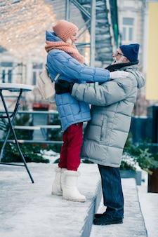 Vrolijk bejaarde echtpaar in de winterdag. vrouw staat hoger dan haar man en legt hand op zijn schouder