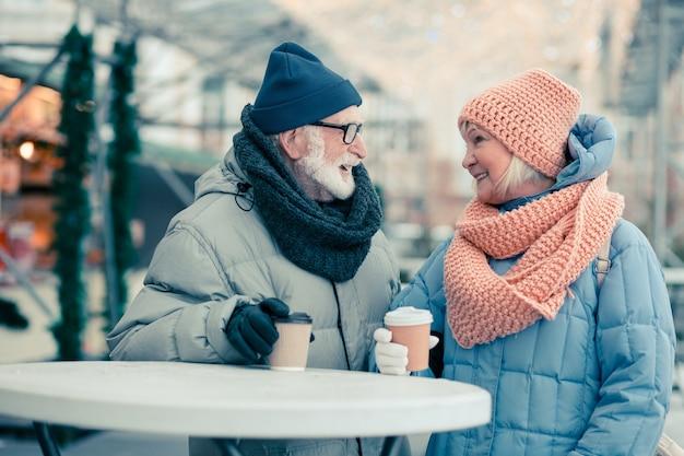Vrolijk bejaarde echtpaar in warme jassen die buiten bij elkaar staan en kartonnen kopjes koffie op de ronde tafel zetten