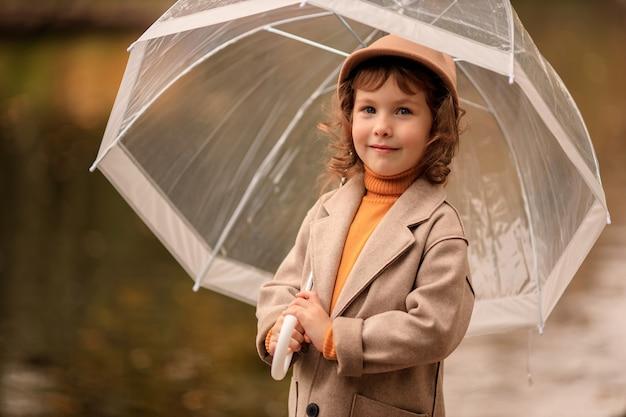 Vrolijk blij meisje met een doorzichtige paraplu op een wandeling in de herfst aan het meer