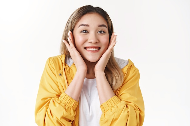 Vrolijk blij mooi glanzend glimlachend gelukkig aziatisch blond meisje aanraking wangen verrast ontvangen positief geweldig nieuws uitgedrukt opwinding opgetogen grijns opgewonden dankbaar triomfantelijk, witte muur