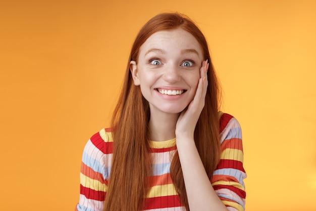 Vrolijk blij opgewonden aantrekkelijk roodharige meisje blozend verrast gevoel blij aanraken wang blij goed nieuws ontvangen staand blij opgewonden geweldige kans krijgen, poseren oranje achtergrond.