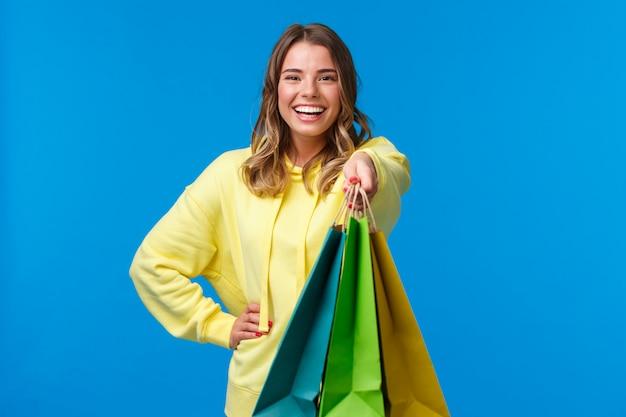 Vrolijk blond meisje dat u boodschappentassen geeft en gelukkig glimlacht, cadeautjes koopt voor een gezinsvakantie, veel personeel in de winkel koopt en vraagt om haar pakketten te dragen, te staan