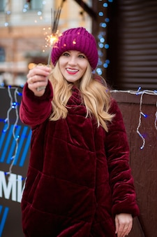 Vrolijk blond meisje gekleed in stijlvolle kleding, met gloeiende sterretjes op de kerstmarkt in kiev