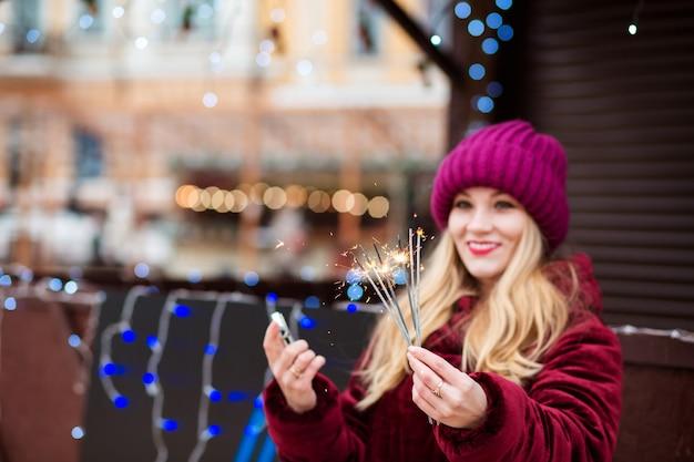 Vrolijk blond meisje met gloeiende bengaalse lichten op de kerstmarkt in kiev. vervagingseffect