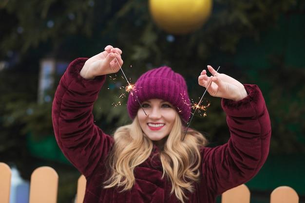 Vrolijk blond model met gloeiende bengaalse lichten bij de belangrijkste kerstboom in kiev. vervagingseffect