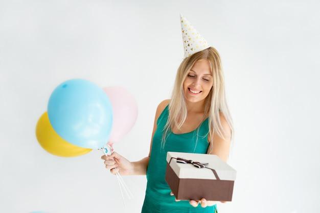 Vrolijk blondemeisje in verjaardagshoed