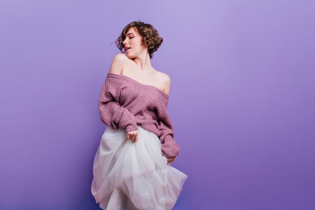 Vrolijk bruinharige vrouwelijk model in trui met plezier op indoor fotoshoot. mooie brunette krullende dame speelt met weelderige witte rok.
