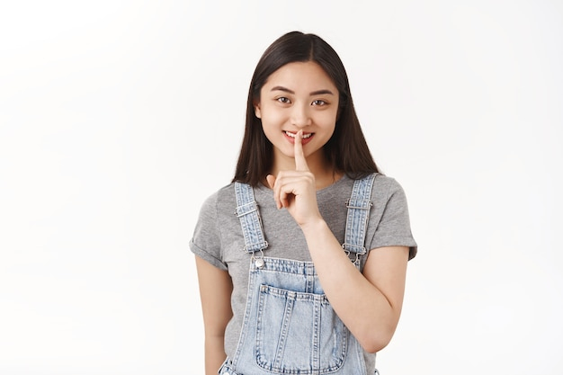 Vrolijk brutaal schattig aziatisch brunette meisje draag denim zomer tuinbroek zwijg glimlachend sluw hebben plan delen mysterie vragen zwijgen maken verrassing witte muur
