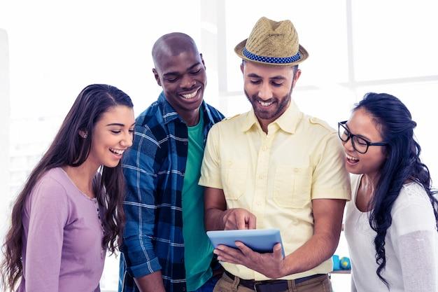 Vrolijk creatief team die tabletpc in bureau met behulp van