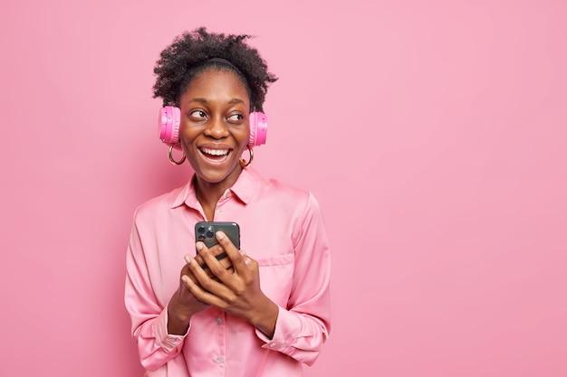 Vrolijk donker gevild krullend vrouwelijk model glimlacht breed luistert naar muziek via draadloze hoofdtelefoons