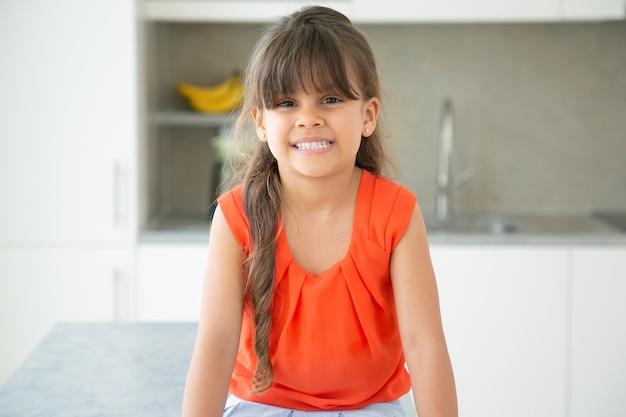 Vrolijk donkerharige latijns-meisje, gekleed in een rood mouwloos shirt, poseren in de keuken
