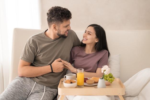 Vrolijk echtpaar dat van ontbijt en huwelijksreis geniet in hotelslaapkamer