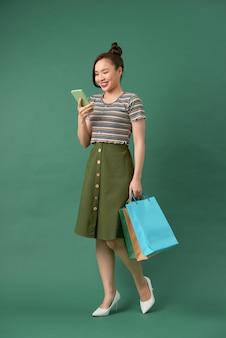 Vrolijk elegant meisje boodschappentassen te houden tijdens het chatten op smartphone op groen