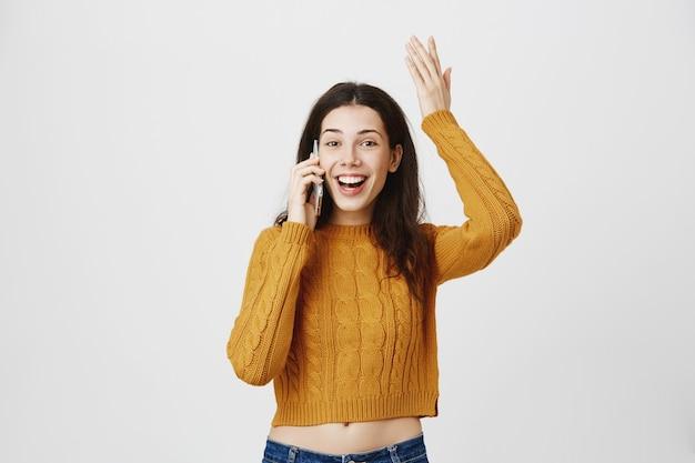Vrolijk en blij meisje ontvangt goed nieuws tijdens een telefoongesprek