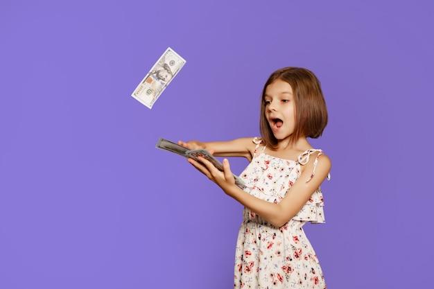 Vrolijk en gek europees tienermeisje gooit geld in haar handen op een paarse achtergrond
