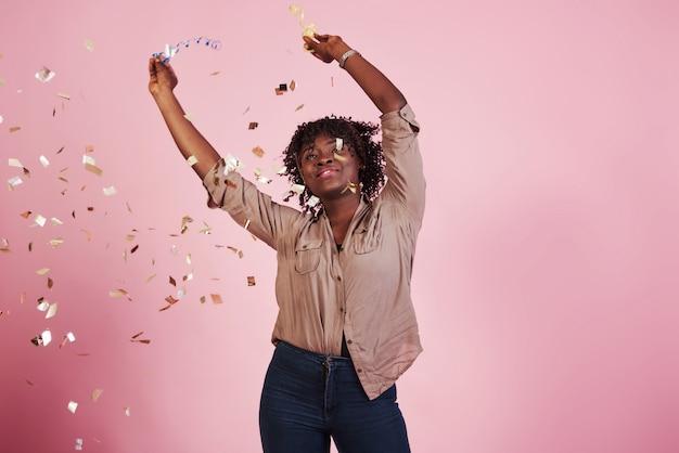 Vrolijk en gelukkig. de confetti in de lucht gooien. afrikaanse amerikaanse vrouw met roze erachter achtergrond