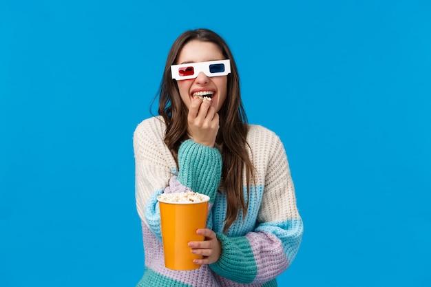 Vrolijk en gelukkig, lachend brunette kaukasisch meisje dat van grappige film geniet, een 3d-bril draagt, grinnikt en popcorn kauwt, doos vasthoudt, in de wintertrui staat, bioscoopaanbieding studentkorting