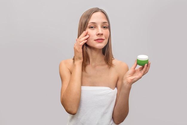 Vrolijk en mooi model staat en poseert. ze houdt een glas gezichtscrème in de hand. jonge vrouw brengt wat lotion op gezicht. ze ziet er gelukkig uit.