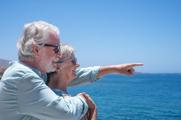 Vrolijk en ontspannen senior paar vooraan naar de zee kijkend naar de horizon over water. twee gepensioneerden genieten van zomer en vakantie