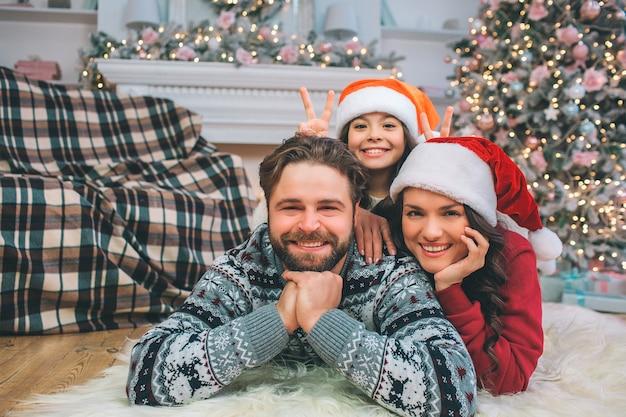 Vrolijk en positief jong gezin dat op de vloer ligt en er recht uit ziet. ze lachen. jonge vrouw en meisje staan achter de man. ze dragen kerstmutsen.