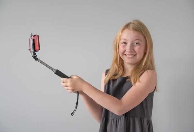 Vrolijk en vrolijk meisje in een grijze jurk met een selfiestick en een rode telefoon maakt een grappige foto of video op een grijze achtergrond