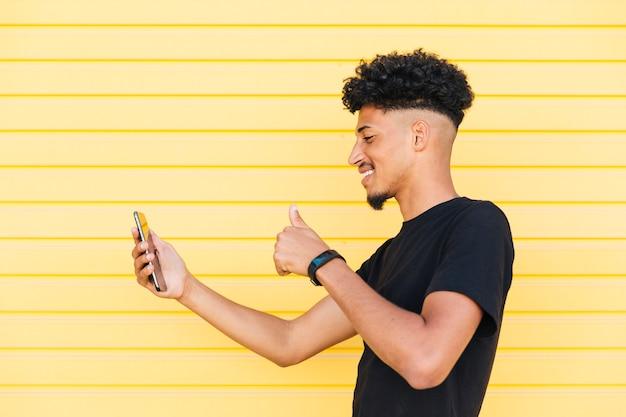 Vrolijk etnisch mannetje die selfie met omhoog duim nemen