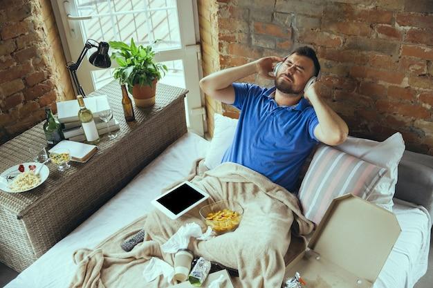Vrolijk, geïnspireerd luisteren naar muziek met een koptelefoon. luie man die in zijn bed woont, omringd door rommelig. je hoeft niet de deur uit om gelukkig te zijn. gadgets gebruiken, film en series kijken, emotioneel. fast food.