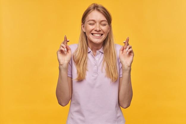 Vrolijk geïnspireerde vrouw met sproeten in lavendelkleurige t-shirt houdt ogen gesloten en vingers gekruist op geel