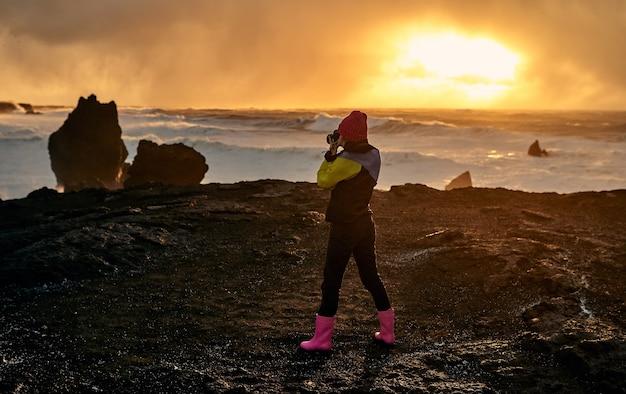 Vrolijk geklede jonge vrouw toerist maakt een foto van een prachtig zeegezicht, staande op de kust met zwart vulkanisch zand bij zonsondergang.