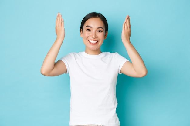 Vrolijk, gelukkig aziatisch meisje opent ogen en lacht vrolijk en verrast, steekt handen omhoog en kijkt vrolijk over blauwe achtergrond, viert verjaardag, wordt verbaasd met cadeau