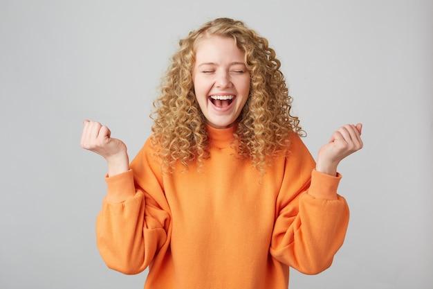 Vrolijk gelukkig blond meisje in oranje trui glimlachend en gebalde vuisten als winnaar met ogen gesloten van plezier
