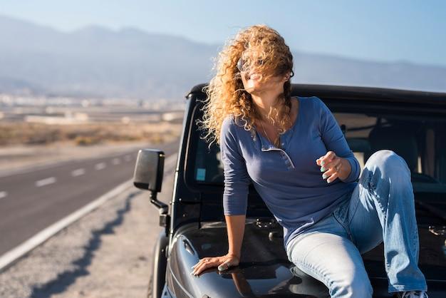 Vrolijk gelukkig, dame zittend op de auto in reizen avontuur vakantie glimlach en genieten van vrijheid - bestuurder en voertuig met weg op de achtergrond - concept van vrolijke single lifestyle mensen