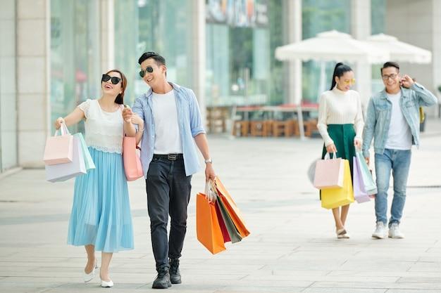 Vrolijk gelukkig jong aziatisch stel dat na het winkelen op straat loopt met papieren zakken