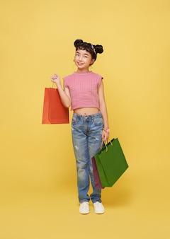 Vrolijk gelukkig jong geitje aziatisch kind dat van winkelen geniet, zij draagt ?? boodschappentassen in het winkelcentrum.