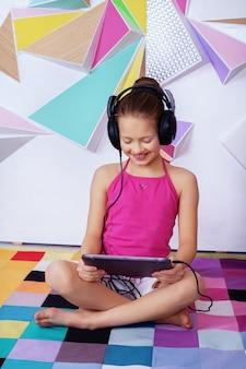 Vrolijk gelukkig kind dat aan een film met hoofdtelefoons luistert